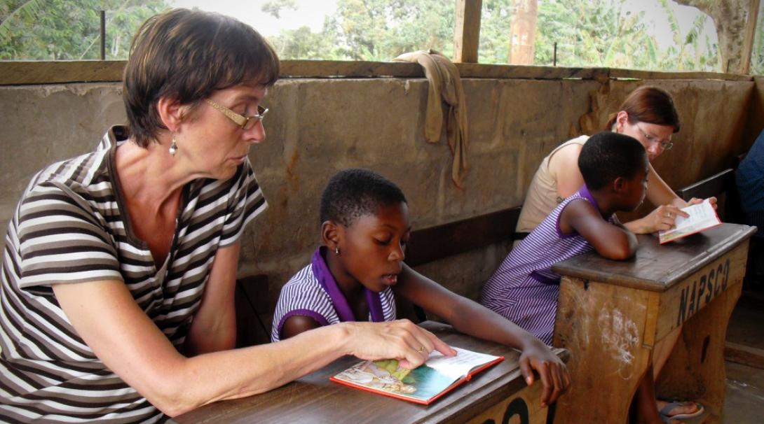 A couple of volunteers doing a teaching English project in Ghana with Projects Abroad participate in a reading club.
